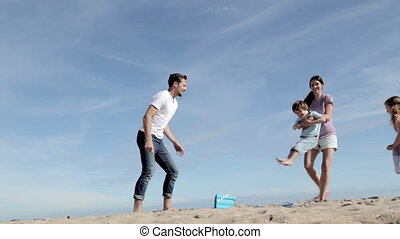Mother and Father Spinning Their Son and Daughter on the Beach