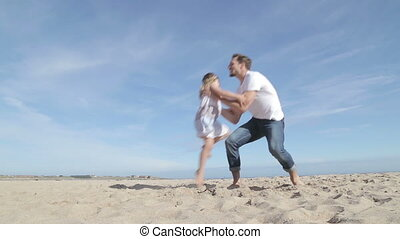 Father Spinning Daughter Round on the Beach - Father picks...