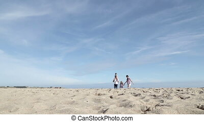 Mother and Father running along the beach with their...