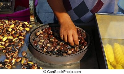 cooking chestnuts - cooking edible chestnuts on a grill in...