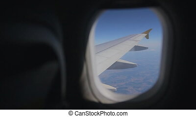 Jet plane flying at high altitude, view of airplane wing...