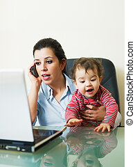 businesswoman on the phone, holding daughter - stressed...