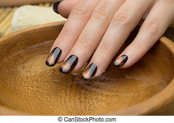 Beautiful woman's nails with nice stylish manicure in the...