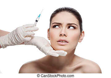 Scared girl looking at syringe - Scared young woman looking...