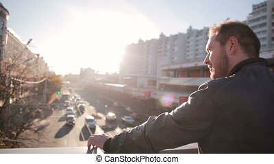 Man looks at traffic in the city in the sunset - Young Man...