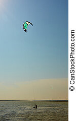 young woman kite-surfer - A young woman kite-surfer rides in...