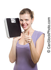 smiling young woman with thumbs up holding a weight scale...