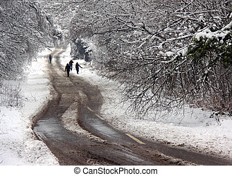 A group of people walking along a winter snow covered road -...