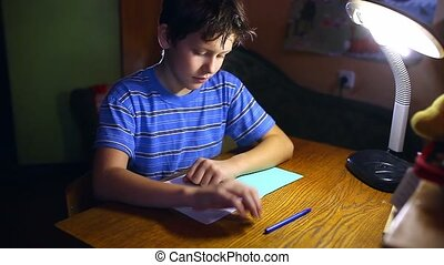 teenage boy writes in notebook homework sitting at lamp...