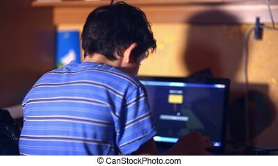 teenage boy playing computer video game sitting back evening...