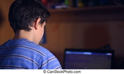 teenage boy playing computer game video sitting back room...