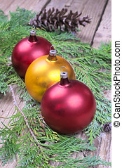 Three colored Christmas balls on pine needles on a wooden...
