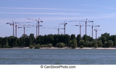 View of construction cranes in park - View from river on...