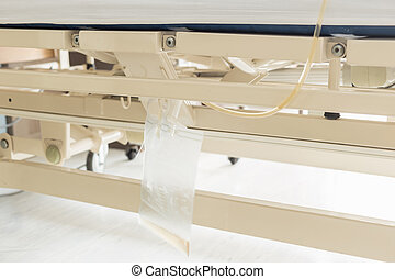 Clear plastic urine bag hang on bed of female patient -...