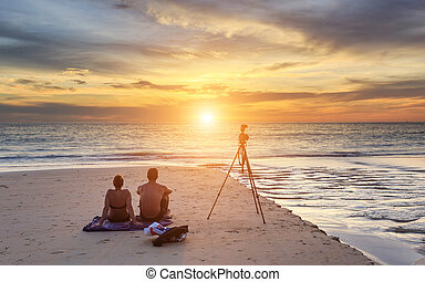 Couple sitting on the sunset beach, in Phuket Thailand