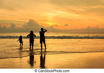 Silhouette of family at the sunset beach in Phuket, Thailand