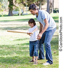 Cheerful father playing baseball with his son in the park