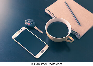 Book and coffee cup on black wooden table background