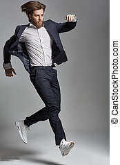 Elegant young guy jumping and dancing - Elegant young man...