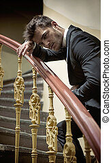 Elegant man leaing on handrail