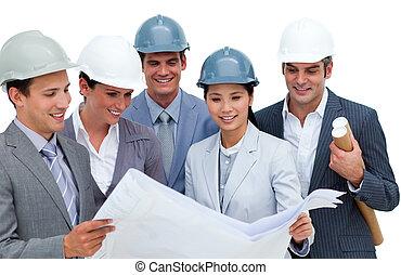 Multi-ethnic architects studying blueprints isolated on a...