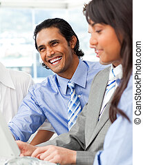 Laughing businessman working with his team in the office