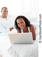 Cheerful couple relaxing on their bed