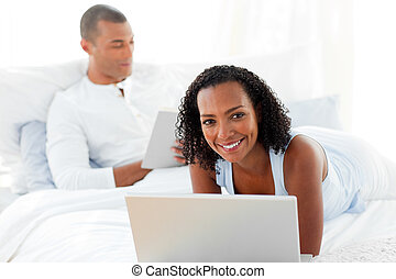 Enamoured couple relaxing on their bed at home