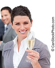 Radiant businesswoman tasting Champagne against a white background