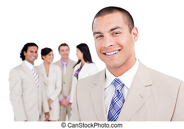 Happy businessman standing in front of his team against a...