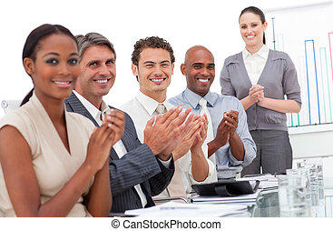 Happy business team applauding a good presentation in the...