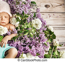 Cute child sleeping on the flowers