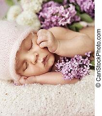 Cute newborn child sleeping on the carpet