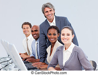 Smiling manager checking his team\'s work in a call center