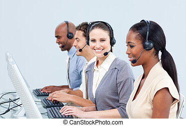 Cheerful customer service representatives using headset in a call-center