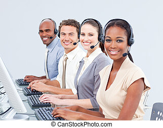 Multi-ethnic customer service representatives using headset...