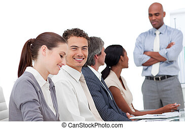 Charming businessman doing a presentation to his team in a...