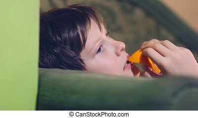 Teenage boy is eating an orange and peel - Teenage boy is...