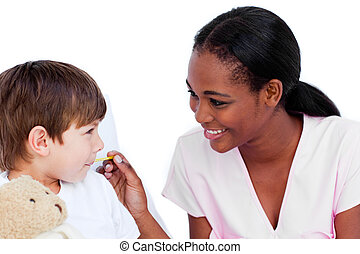 Smiling doctor taking child\'s temperature in a hospital