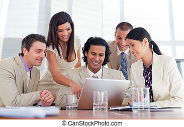 Cheerful business partners working at a computer in a...