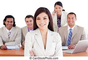 Assertive manager with folded arms in front of her team in...