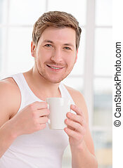 Young handsome guy enjoys his cup of coffee - Coffee boost...