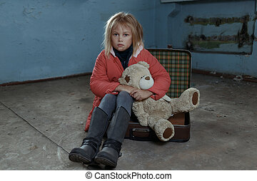 Lonely girl sitting on the suitcase - In dire need Poor...