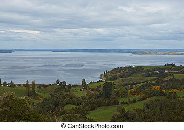 Aquaculture in Chiloe - Lush vegetation and fields on the...