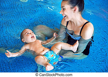 Young mother and baby relaxing in the swimming pool