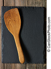 Wooden spatula on slate background