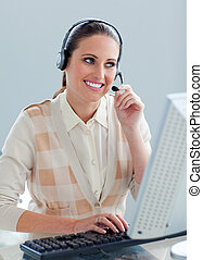 Assertive businesswoman with headset on working at a...