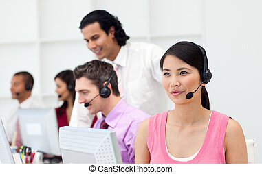 Portrait of a positive business team working in a call...