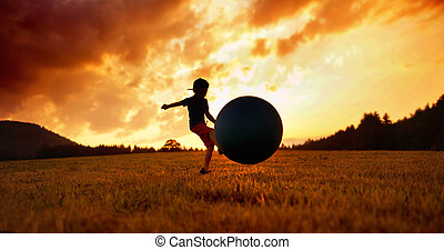 Little boy playing football on the meadow