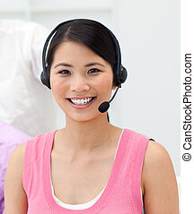 Charming young businesswoman talking on headset in the...